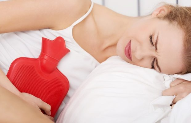 Beautiful caucasian woman lying with hot water bag
